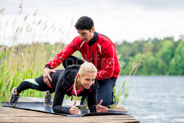 Woman with personal trainer doing fitness push-up Stock photo © Kzenon