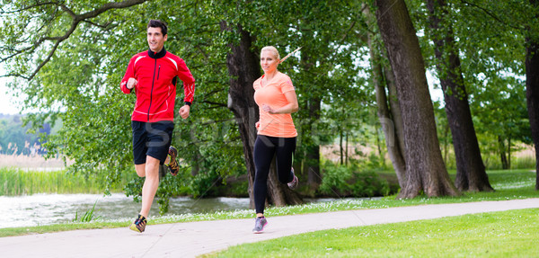 Woman and man jogging on dirt path in the woods together  Stock photo © Kzenon