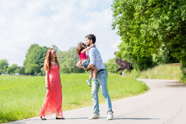 Mom, dad and daughter having walk on path Stock photo © Kzenon