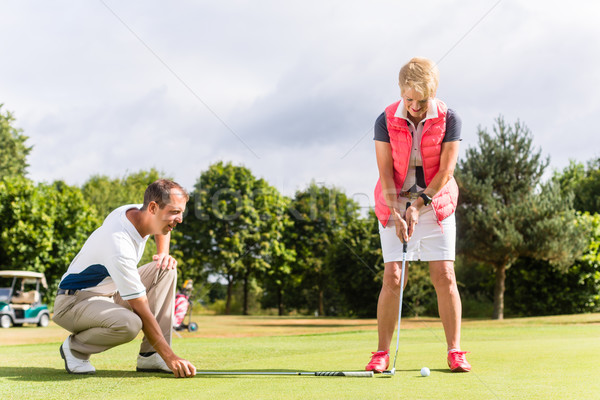 Senior woman and golf pro practicing their sport Stock photo © Kzenon