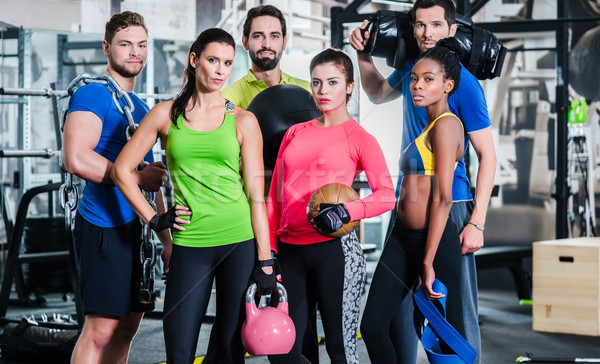 Group of women and men in gym posing at fitness training Stock photo © Kzenon