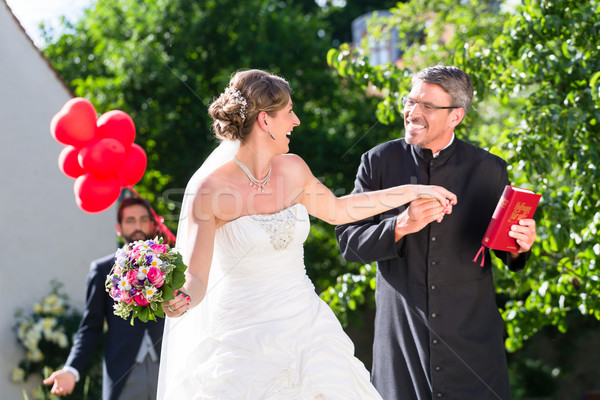 Stock photo: Bride running away with priest after wedding