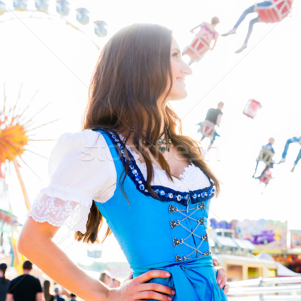 woman wearing dirndl standing in front of ferris wheel Stock photo © Kzenon