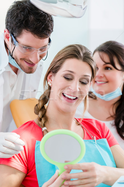 Woman after dental bleaching at dentist Stock photo © Kzenon