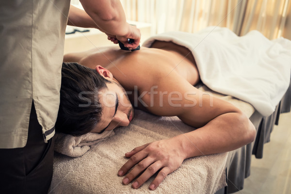 Young man relaxing during traditional massage with hot stones Stock photo © Kzenon