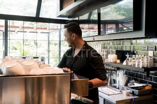 Young man working as barista behind the bar counter of a clean a Stock photo © Kzenon