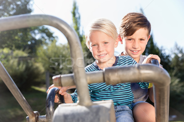 Two boys using digger on adventure playground in park Stock photo © Kzenon