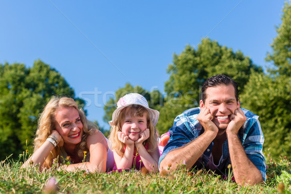 Father, mother, daughter lying on meadow in grass Stock photo © Kzenon