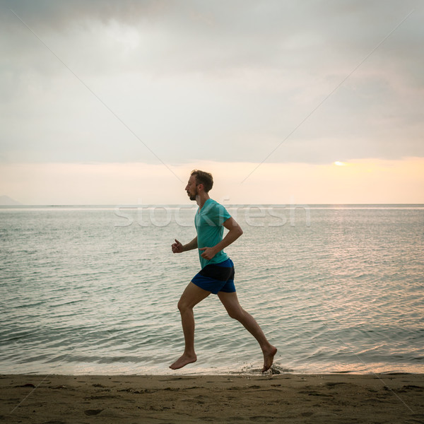 Athletic young man running on the beach during cardio workout session Stock photo © Kzenon
