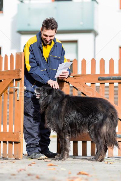 Big black dog welcoming postman at garden gate Stock photo © Kzenon
