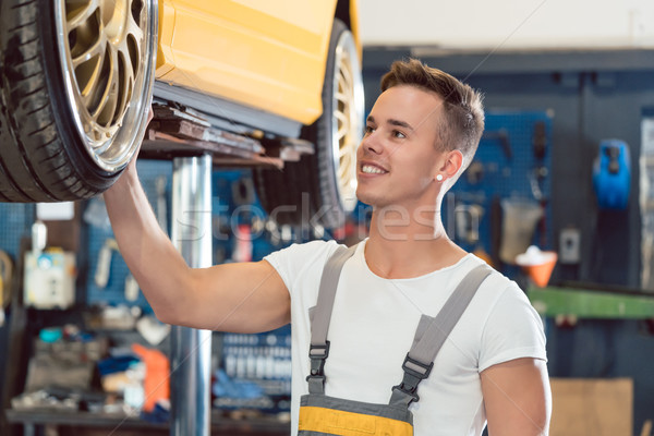 Portrait of a car tuning specialist smiling while checking wheels of tuned car Stock photo © Kzenon