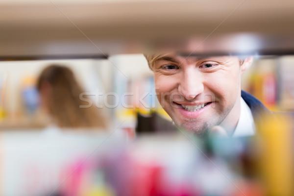 Man looking through shelf of books choosing volume to read in library Stock photo © Kzenon