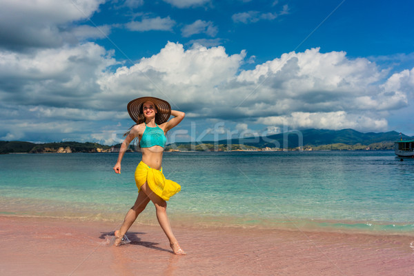 Fashionable woman enjoying a walk on a tropical beach Stock photo © Kzenon
