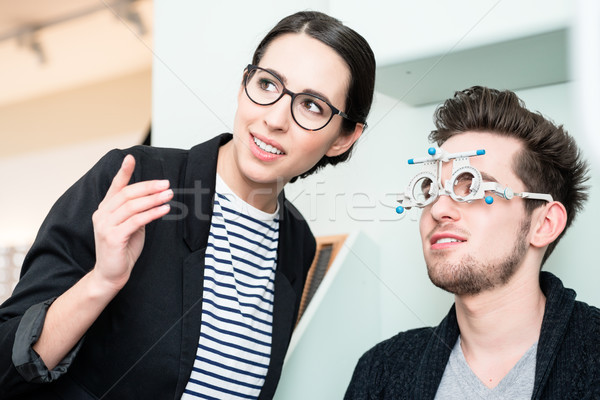 Man with optician at eyesight test for glasses Stock photo © Kzenon