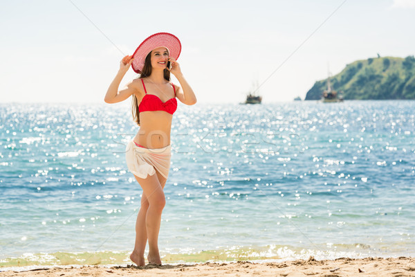 Fashionable fit young woman talking on mobile phone on the beach Stock photo © Kzenon