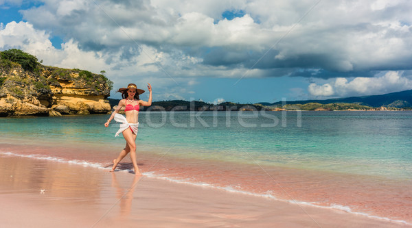 Happy young woman walking through shallow sea water on the beach Stock photo © Kzenon