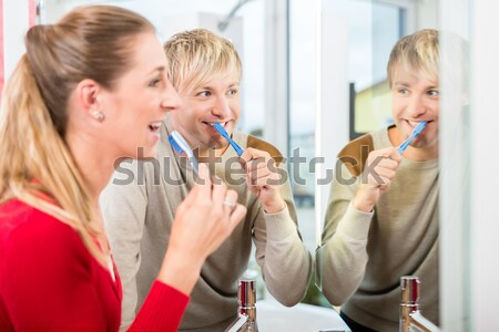 Dentist showing senior patient samples of teeth colors Stock photo © Kzenon