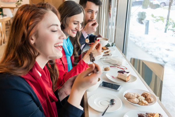 Three colleagues smiling while eating delicious cakes during break Stock photo © Kzenon