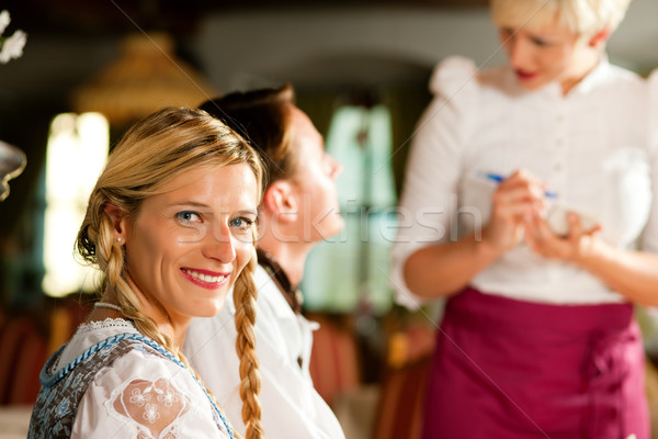 Waitress in Bavarian restaurant taking orders Stock photo © Kzenon