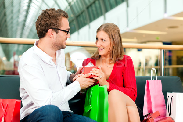Man with gift for woman in mall Stock photo © Kzenon