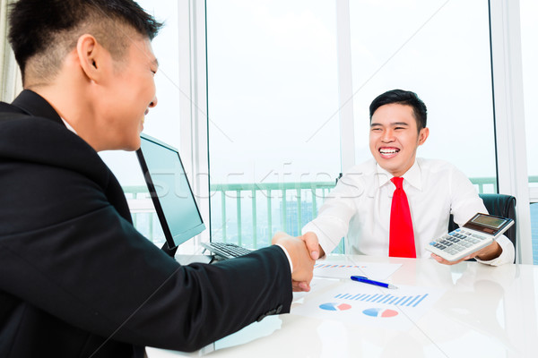 Stock photo: Asian banker advising on financial investment