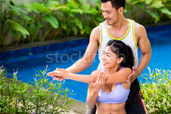 Asian woman with trainer at fitness workout Stock photo © Kzenon