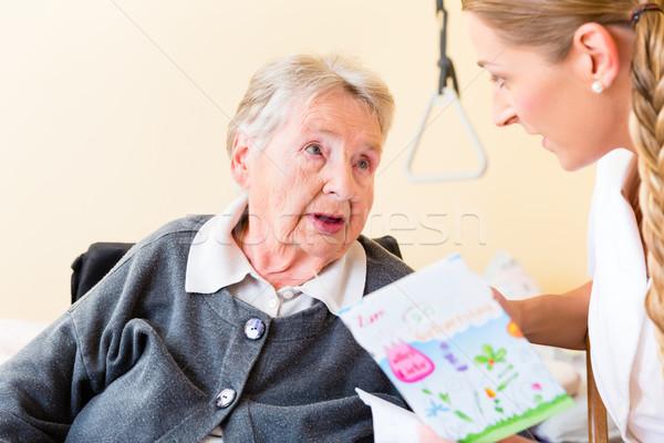 Nurse giving birthday card to senior woman in home Stock photo © Kzenon