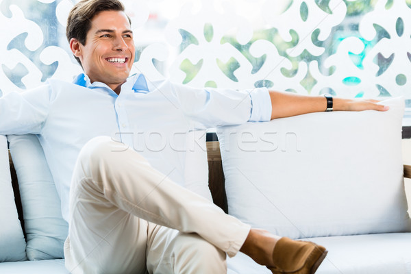 Man sitting on couch in furniture store showroom Stock photo © Kzenon