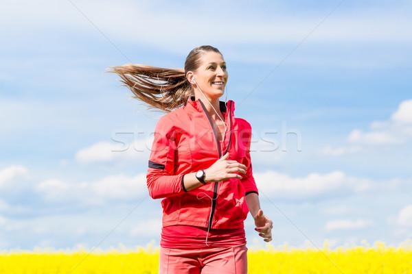 Woman running for better fitness in spring Stock photo © Kzenon