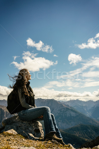 Woman on mountain hike having rest sitting on rock looking into  Stock photo © Kzenon