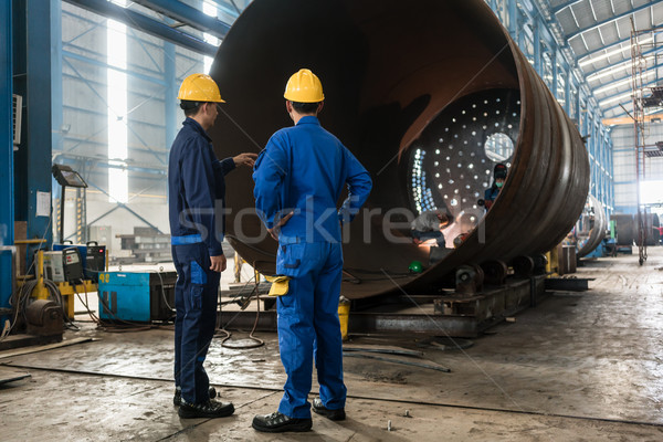 Workers supervising the manufacture of a metallic cylinder  Stock photo © Kzenon