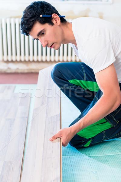Handyman flooring in home construction site Stock photo © Kzenon