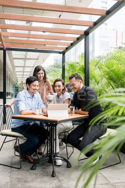 Four Asian young friends watching together funny online content Stock photo © Kzenon