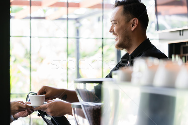 Friendly bartender serving a short espresso to a customer Stock photo © Kzenon