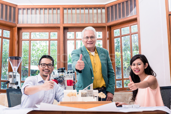 Team of three successful architects showing thumbs up Stock photo © Kzenon