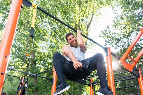 Powerful young man doing one-arm pull-ups while hanging on a bar in park Stock photo © Kzenon