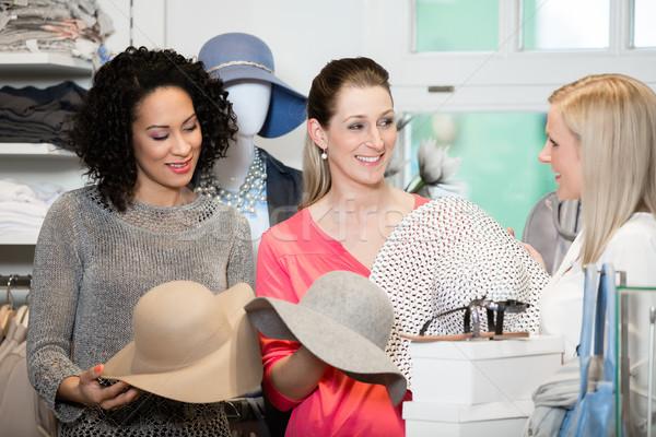Girlfriends on shopping spree trying ladies hats Stock photo © Kzenon