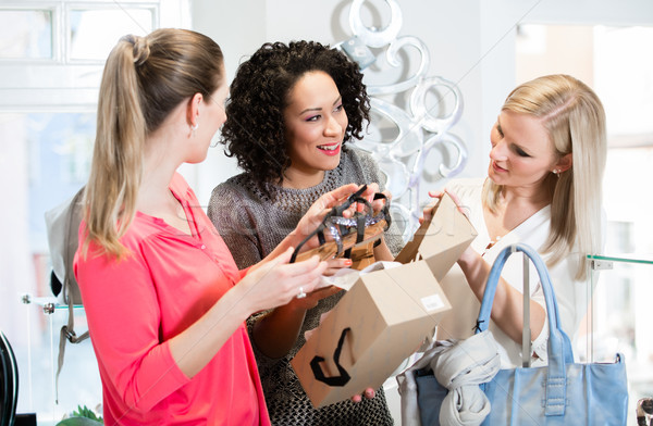 Friends on a shopping trip discussing sandals and shoes Stock photo © Kzenon