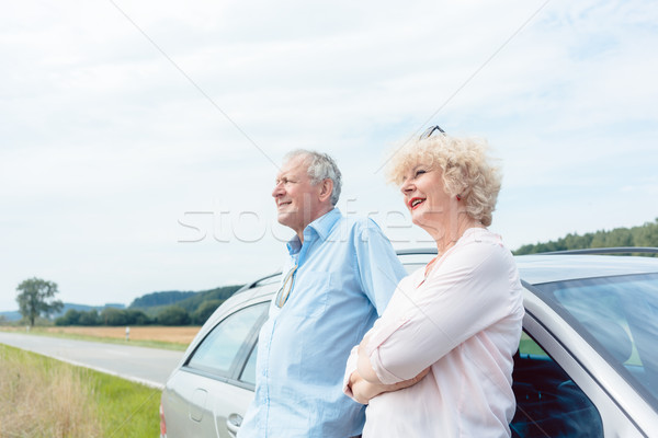 Two senior people smiling with confidence while leaning on their car Stock photo © Kzenon
