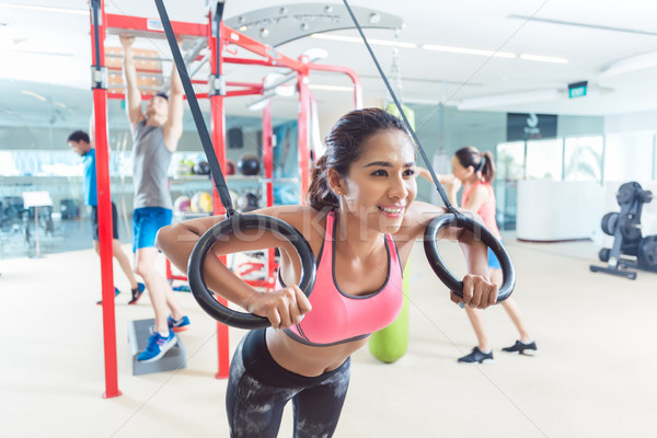 Fit young woman exercising with gymnastic rings in a trendy fitness Stock photo © Kzenon