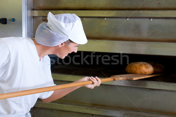 Female baker baking fresh bread in the bakehouse Stock photo © Kzenon