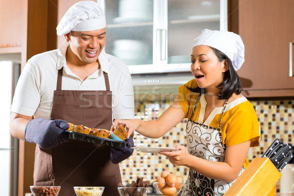 Asian couple baking muffins in home kitchen Stock photo © Kzenon