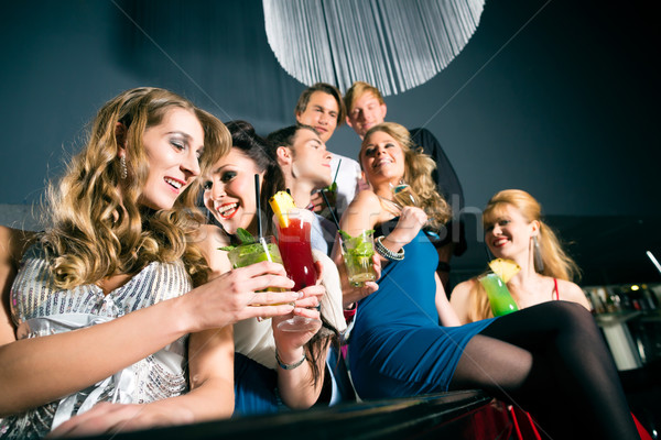 People in club or bar drinking cocktails Stock photo © Kzenon