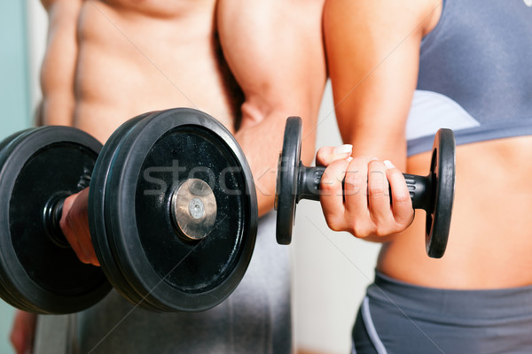 Couple exercising with dumbbells in a gym, focus on the weights, only torso of man and woman to be s Stock photo © Kzenon