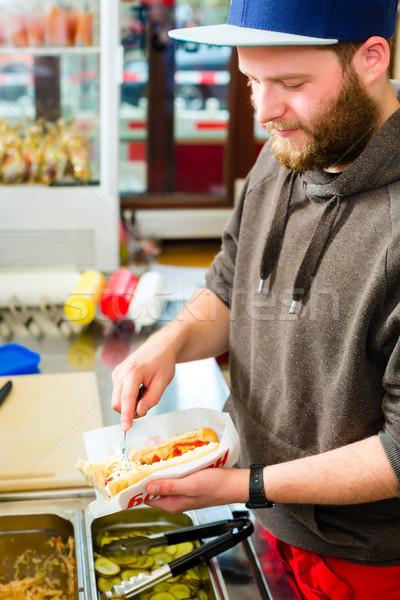 salesman making hotdog in fast food snack bar Stock photo © Kzenon