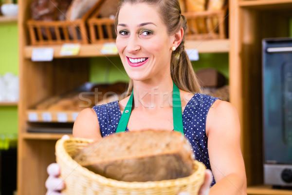 Bakery saleswoman offering bread Stock photo © Kzenon
