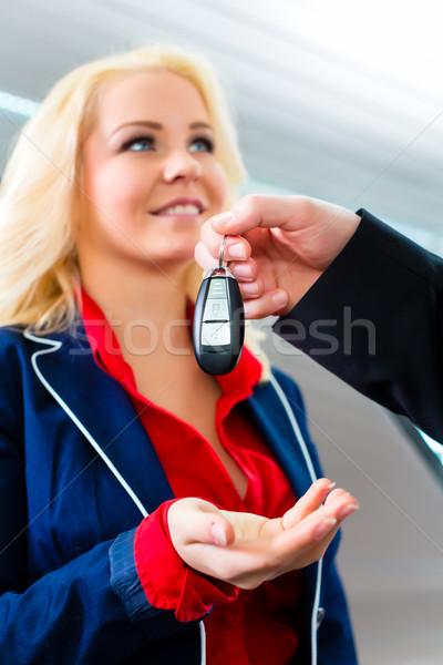 Woman with key to new auto in car dealership Stock photo © Kzenon