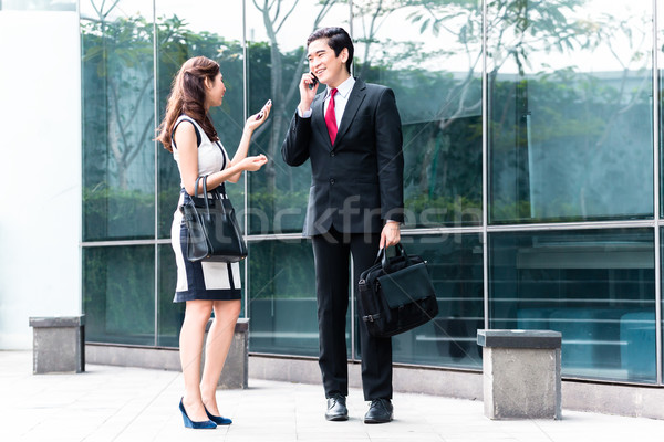 Asian businesspeople talking to cell phones outside Stock photo © Kzenon