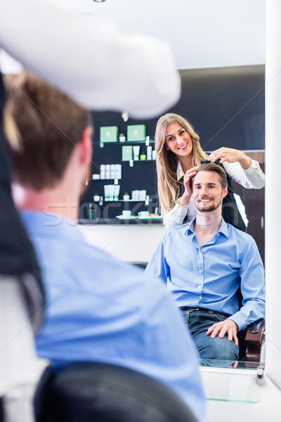 Haircutter cutting hair, shot in mirror Stock photo © Kzenon