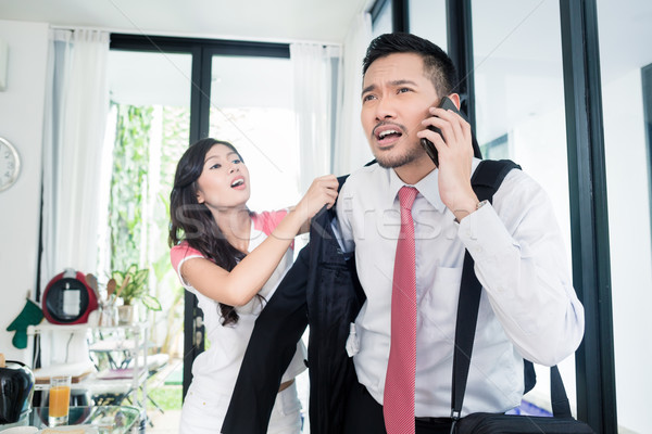 Wife helping man being late for work in jacket Stock photo © Kzenon